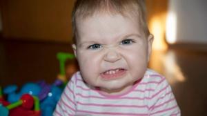 Ein süßes, lustiges Babyfoto, Baby fletscht die Zähne.