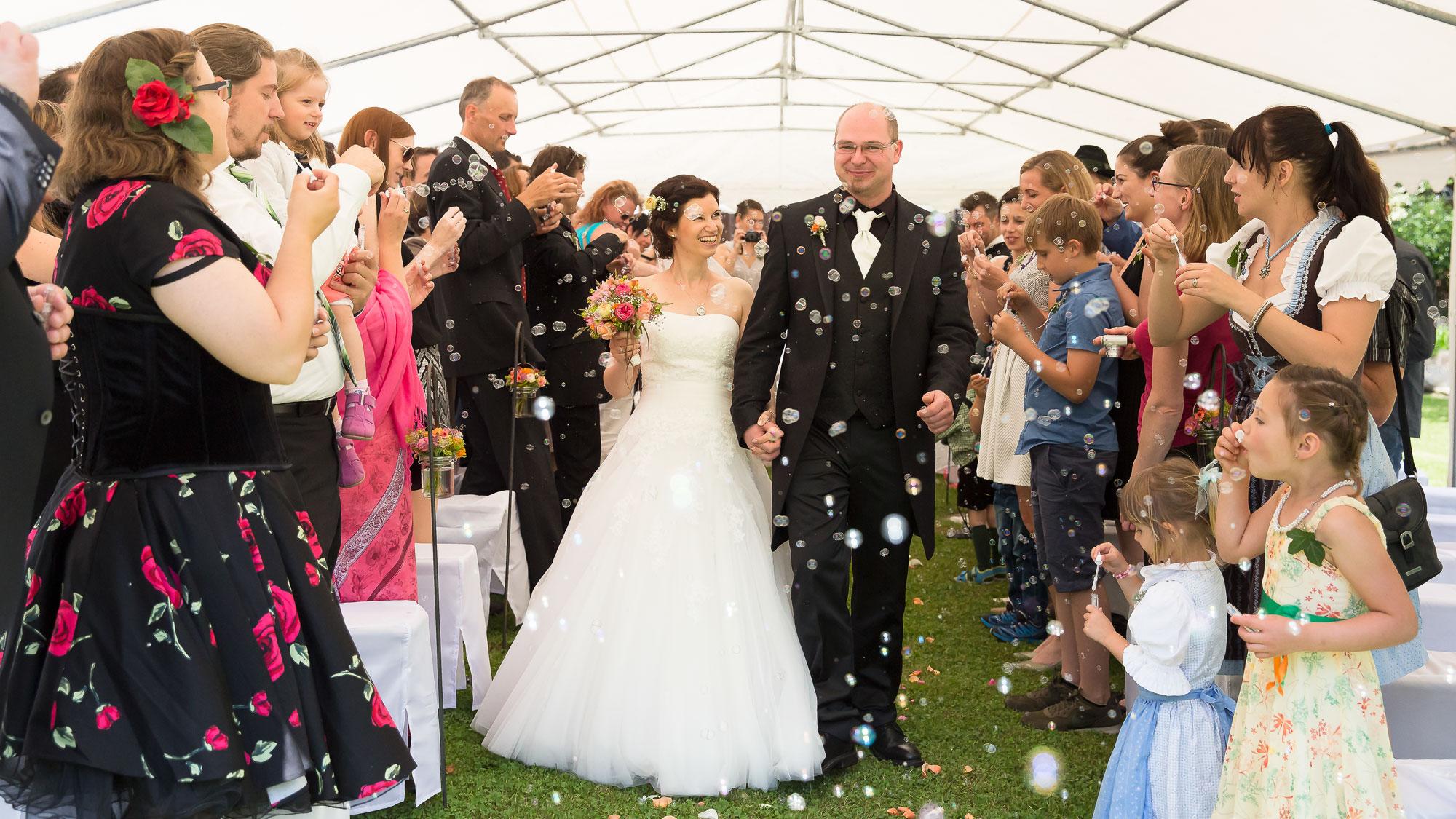 Frisch verheiratet geht es durch Seifenblasen weiter zum Gruppenfoto.