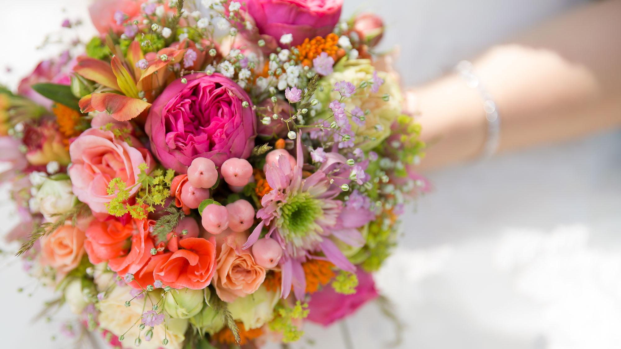 Ein wunderschöner, bunter Brautstrauß wird von der Braut gehalten.