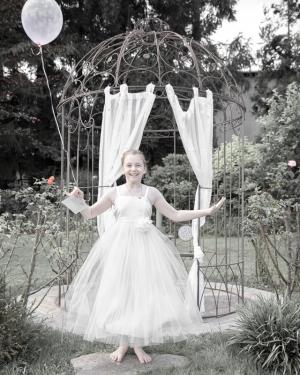 Mädchen in weißen Kleid mit Luftballon vor