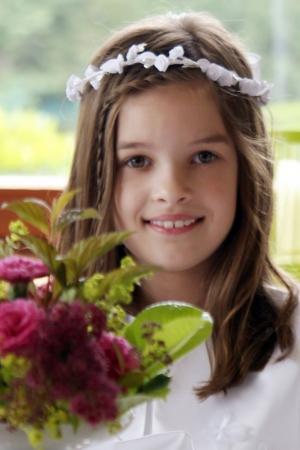 Erstkommunionkind mit einem Lächeln und weißen Blumenkranz