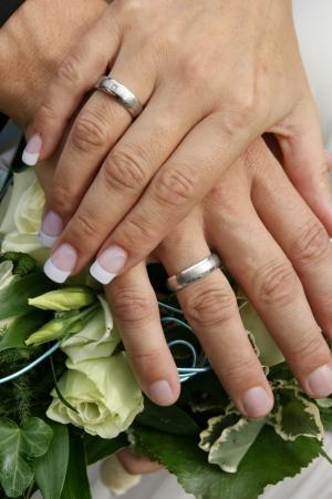 Hochzeitsfotografie ein Brautstrauß mit beiden Händen von den Brautleuten und den Eheringen.