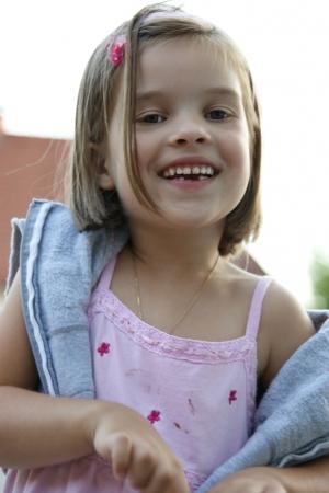 Kinderfotografie von einem freundlichen strahlenden Mädchen.