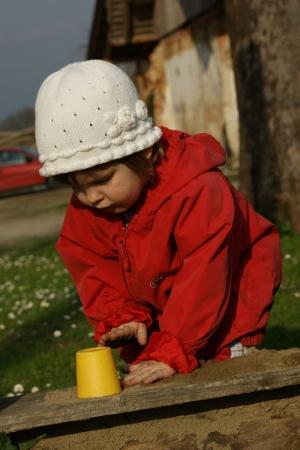 Kinder und Babyfotografie, Kind beim Sandkasten spielen.
