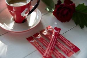 Eine frische Tasse Kaffee, eine rote Rose auf einem Tablett. Die Zuckertüten sind in der Strichform von der Zahl 5 angeordnet.