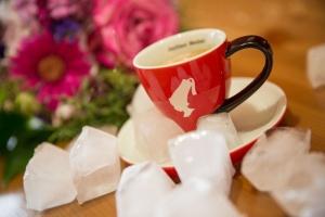Eine heiße frische Tasse Kaffee und zum Kontrast die kalten Eiswürfel, dahinter ein Strauß schöner Blumen.